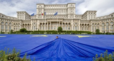 In this May 9, 2013 file picture a worker pulls a huge European Union flag, in Bucharest, Romania, backdropped by the communist era built House of the People. Under communism, religion was not banned, but church going was discouraged for Communist Party members and the Securitate secret police. One dozen churches were razed or moved in Bucharest for Ceausescu's giant House of the People (also inspired by his trip to Pyongyang), but Romania has changed dramatically in the 25 years since the people rose up against dictator Nicolae Ceausescu, executed him and began the slow transformation to a market economy and democracy.  (AP Photo/Vadim Ghirda, File)